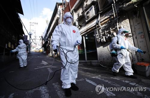 Volunteer workers disinfect a street in Itaewon in the central Seoul ward of Yongsan on May 12, 2020. (Yonhap)