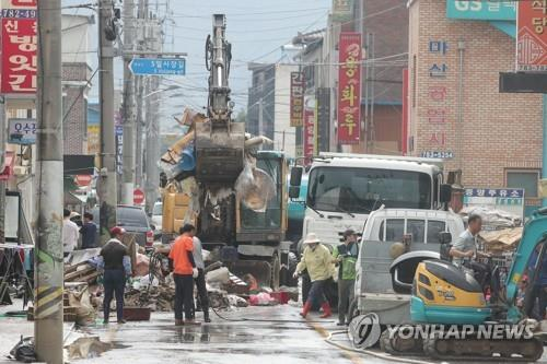 Work to restore a flood-damaged traditional market is under way in Gurye, South Jeolla Province, on Aug. 11, 2020. The entire county was inundated by heavy rains. (Yonhap)