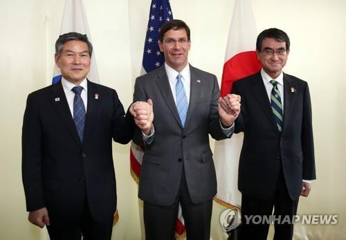 U.S. Secretary of Defense Mark Esper (C) holds the hands of South Korean Defense Minister Jeong Kyeong-doo (L) and his Japanese counterpart, Taro Kono, ahead of their trilateral talks in Bangkok on Nov. 17, 2019. (Yonhap)