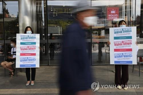Doctors at Seoul National University Hospital in Seoul hold signs on Aug. 23, 2020, in protest of the government's plan to increase medical school admission quotas. (Yonhap)