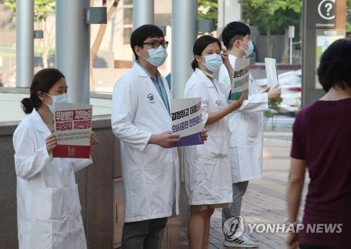 Doctors hold up signs criticizing the government at a Seoul hospital on Aug. 26, 2020, as tens of thousands of doctors went on a full-scale strike nationwide for a three-day run earlier in the day in protest of the government's medical workforce reform. (Yonhap)