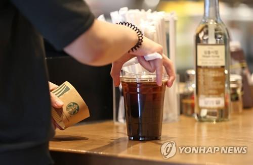 An undated file photo of a citizen ordering coffee for takeaway at a franchise coffee chain in Seoul (Yonhap)