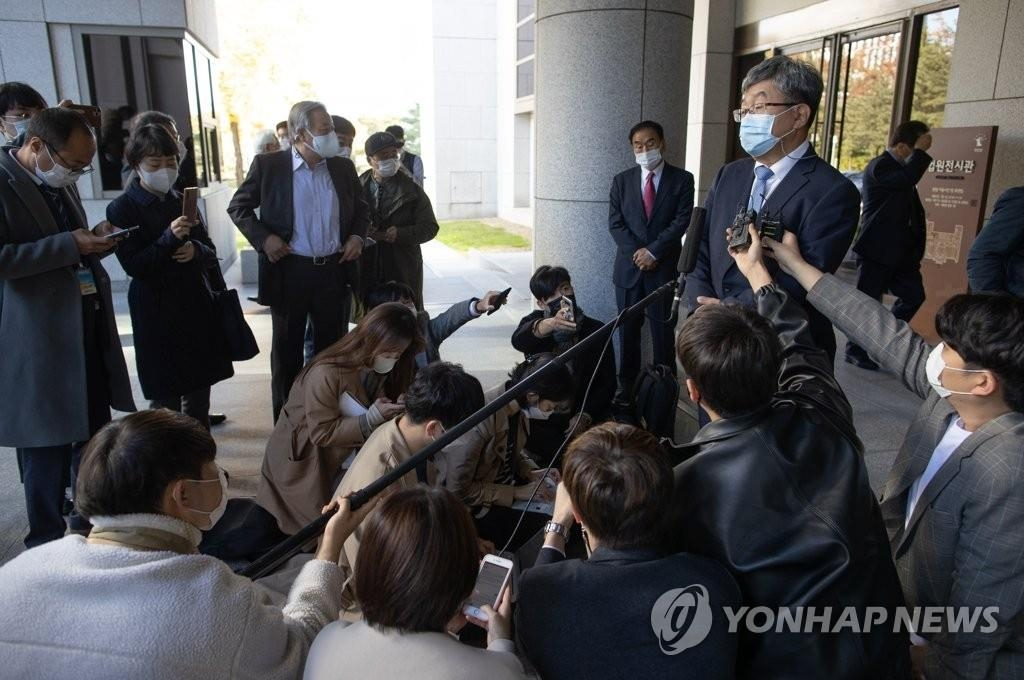 Kang Hun (R), a lawyer for former President Lee Myung-bak, talks to reporters outside the Supreme Court in Seoul after the court upheld a 17-year prison sentence for Lee in a corruption case on Oct. 29, 2020. (Yonhap)