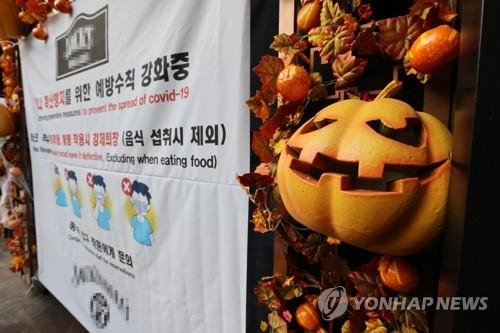 A sign about tougher anti-coronavirus measures is attached to a gate of a shop in Itaewon, central Seoul, on Oct. 29, 2020. The U.S. Forces Korea (USFK) has placed the popular nightlife district off-limits for the upcoming Halloween weekend to prevent the spread of the new coronavirus. (Yonhap)
