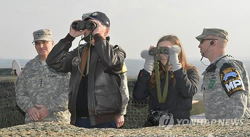 This file photo, taken on Dec. 8, 2013, shows then U.S. Vice President Joe Biden (L), along with his granddaughter, looking at North Korea through binoculars during a visit to a guard post near the Demilitarized Zone (DMZ). (Yonhap)