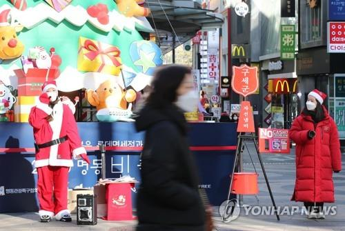 Officials of South Korea's Salvation Army hold its annual charity pot campaign in Seoul's shopping district of Myeongdong on Dec. 20, 2020, amid the new coronavirus outbreak. (Yonhap)