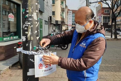 Seo In-young, a resident of Ilsan, northwest of Seoul, checks a hand sanitizer bottle in his neighborhood in this photo provided by Seo. (PHOTO NOT FOR SALE) (Yonhap)
