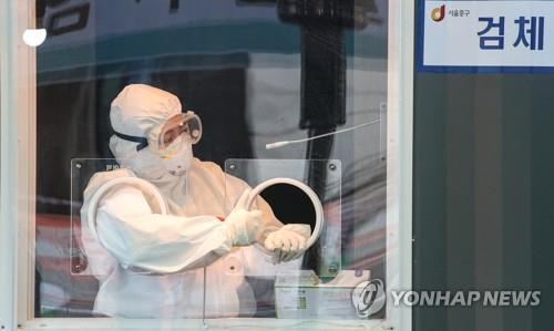 A medical worker waits for visitors to come for coronavirus tests at a makeshift clinic at the plaza in front of Seoul City Hall on Jan. 14, 2021. (Yonhap)