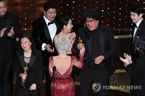 "In this file photo released by AFP, ""Parasite"" director Bong Joon-ho (2nd from R) accepts the best picture award for the film during the 92nd Oscars at the Dolby Theatre in Los Angeles on Feb. 9, 2020. (PHOTO NOT FOR SALE) (Yonhap)"