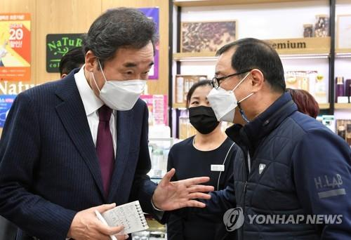 This photo provided by the National Assembly press corps shows Democratic Party Chairman Rep. Lee Nak-yon talking to a business owner in Seoul on Jan. 14, 2021, while inspecting business establishments hit by the new coronavirus pandemic. (PHOTO NOT FOR SALE) (Yonhap)