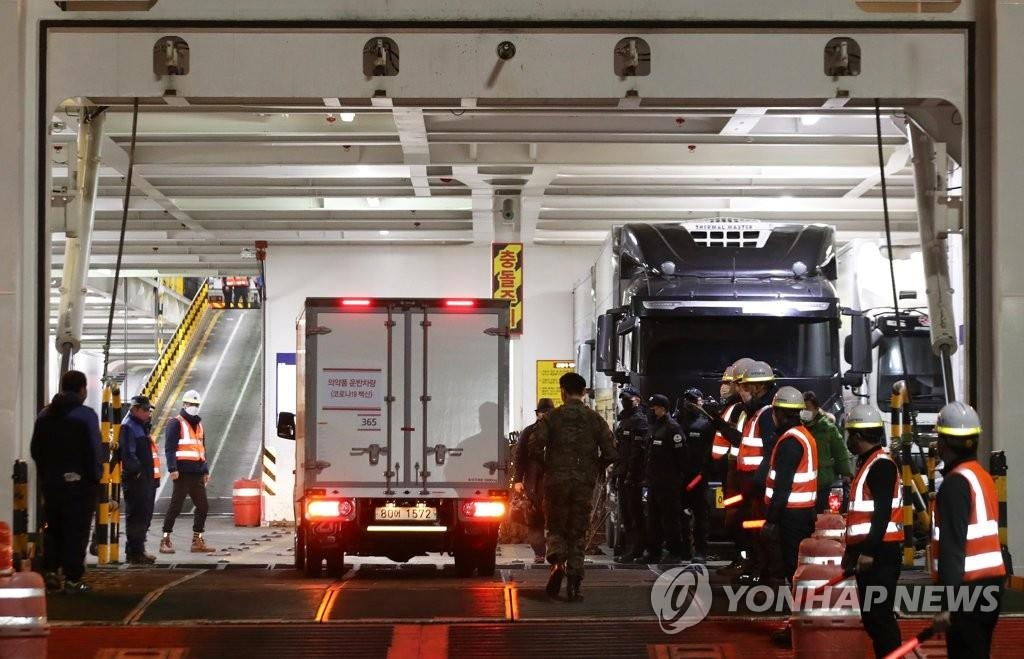 A truck carrying AstraZeneca's vaccine drives onto a car ferry at the southwestern port of Mokpo under the escort of the military and police in the wee hours of Feb. 25, 2021, to head for the country's southern Jeju Island. (Yonhap)