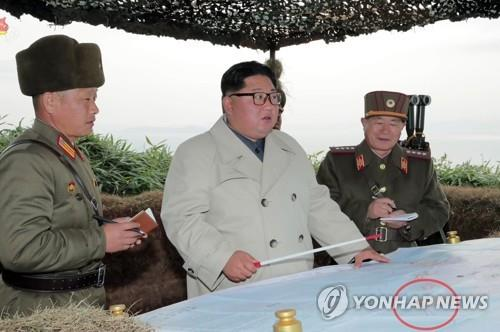 North Korean leader Kim Jong-un (C) talks with military officers during his visit to a defense detachment on Changrin Islet near the de facto western sea border with South Korea in this image captured from the North's Korean Central Television on Nov. 25, 2019. The map in front of them has a mark (in the red circle), which appears to indicate that the firing drills of the coastal artillery company on the islet target the South. (For Use Only in the Republic of Korea. No Redistribution) (Yonhap)