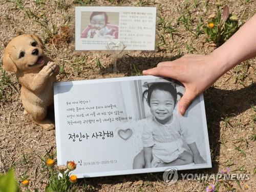 Photos of Jung-in, a 16-month-old child who was abused to death at the hands of her adoptive parents, are placed at her cemetery in Yangpyeong, Gyeonggi Province, on May 14, 2021. (Yonhap)
