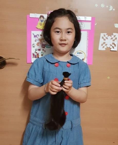 소아암 어린이에게 기부할 모발을 들고 있는 최지우 양 [대전 중앙유치원 제공=연합뉴스]
