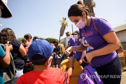 7일(현지시간) 미국 LA의 한 YMCA에서 간호사와 의료 종사자들이 학생들에게 학용품 등이 담긴 가방을 나눠주고 있다. [AFP=연합뉴스]