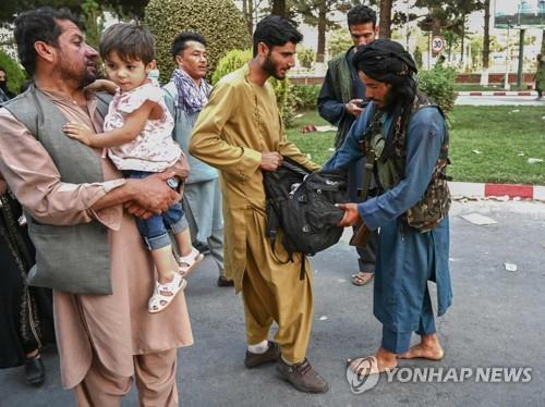 아프간 수도 카불의 국제공항에서 나오는 주민의 짐을 검사하는 탈레반 조직원(오른쪽). [AFP=연합뉴스]