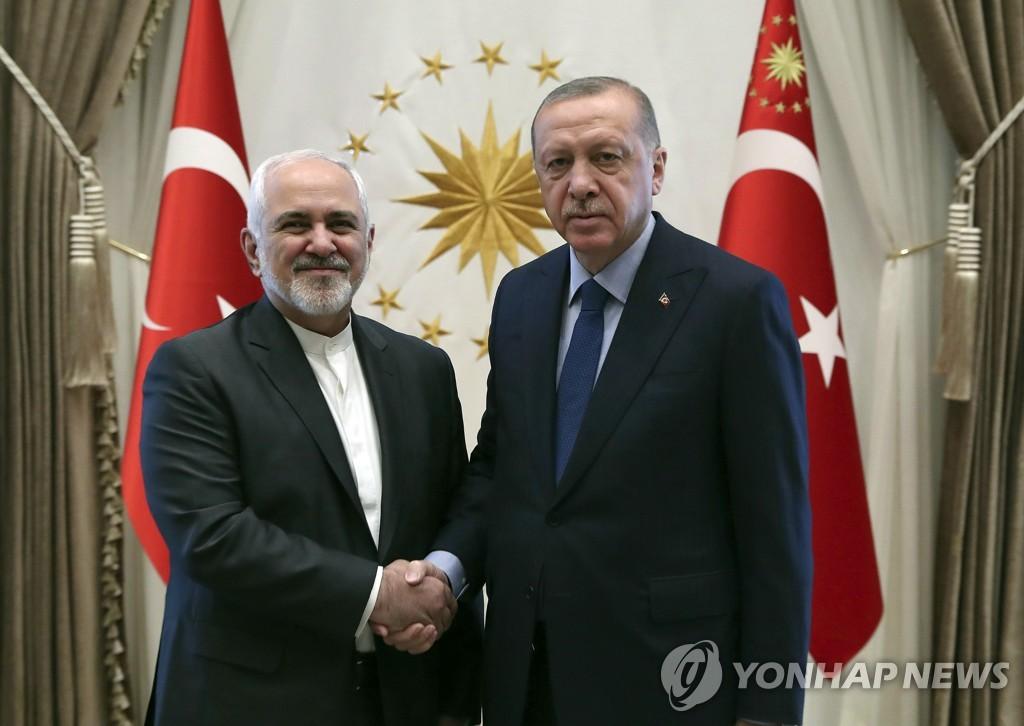 이달 17일 터키 방문한 자리프 이란 외무장관(왼쪽)과 악수하는 에르도안 대통령