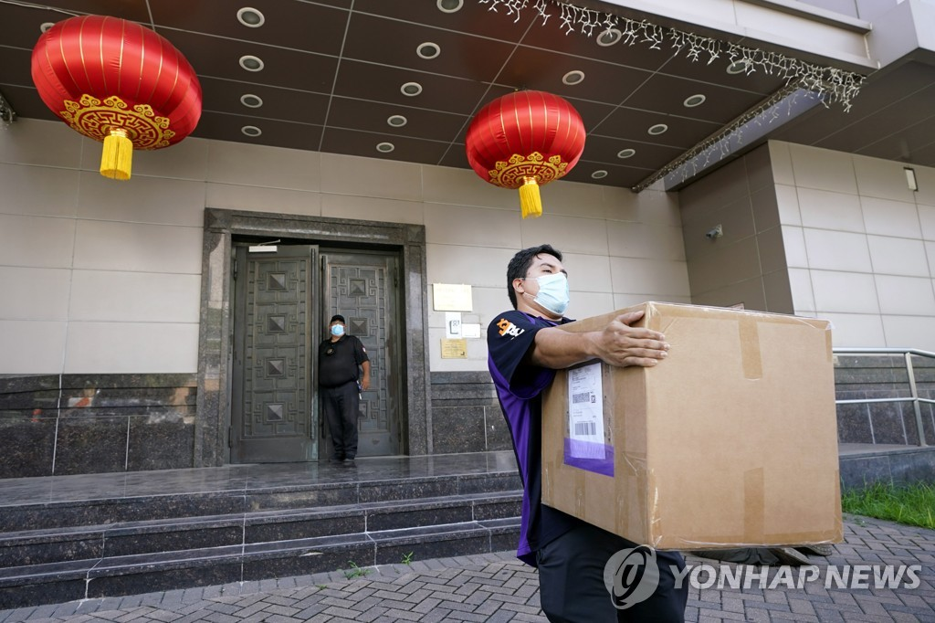 "This AP photo, taken on July 23, 2020, show a FedEx worker removing a box from the Chinese Consulate in Houston, Texas, one day after the U.S. ordered the Chinese consulate to be shut down, citing what it called ""espionage"" activities by Chinese diplomats there. (PHOTO NOT FOR SALE) (Yonhap)"