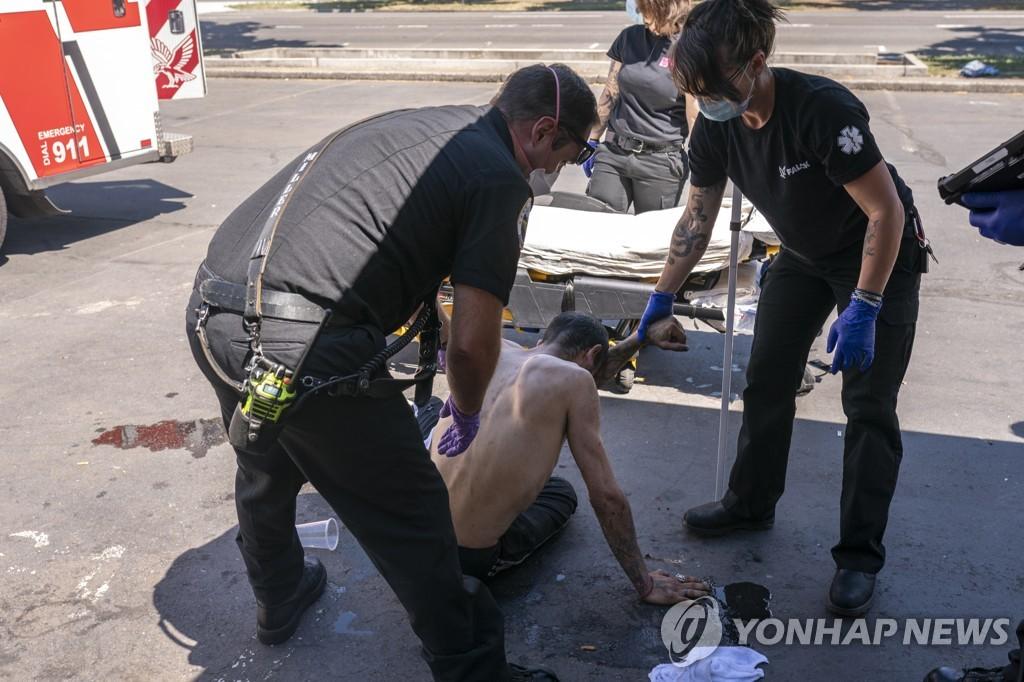 오리건주 세일럼에서 구조대원들이 폭염으로 지친 남성을 돕고 있다. [AP=연합뉴스]