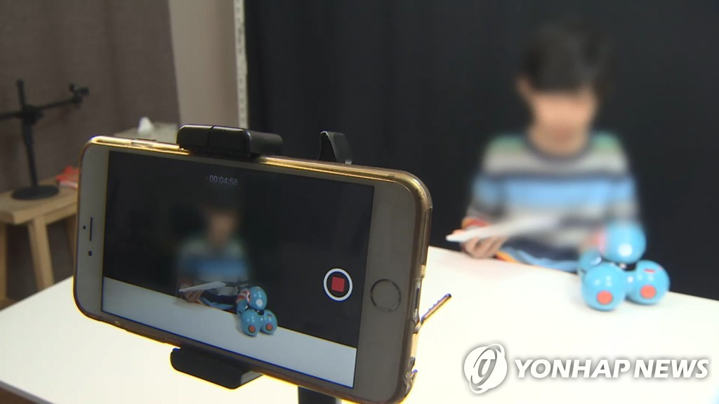 This file photo shows a child talking in front of a mobile phone camera. (Yonhap)