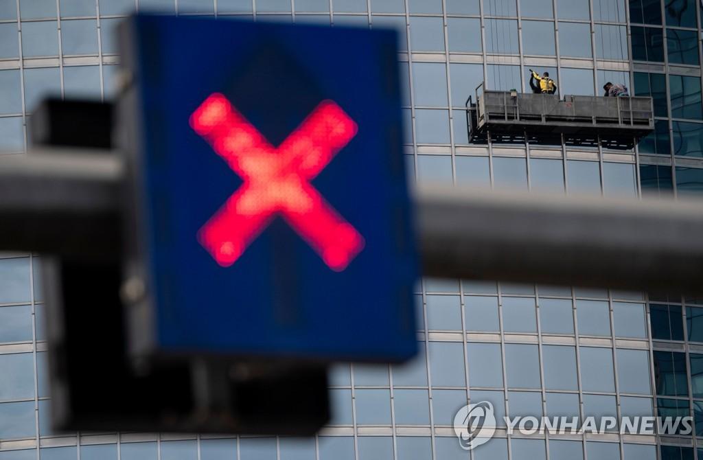 지난 16일 중국 베이징의 한 빌딩에서 근로자가 창문을 닦고 있는 가운데 신호등에 'X' 표시가 켜진 모습