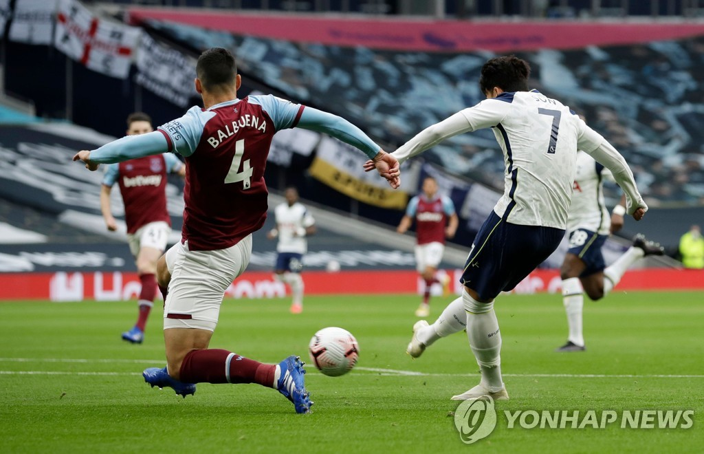 In this AFP photo, Son Heung-min of Tottenham Hotspur (R) scores past Fabian Balbuena of West Ham United during a Premier League match at Tottenham Hotspur Stadium in London on Oct. 18, 2020. (Yonhap)