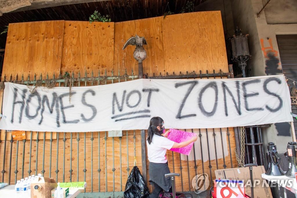 미국 로스앤젤레스에서 강제퇴거에 반대하며 노숙인들에게 음식을 나눠주는 세입자단체 활동가들[AFP=연합뉴스 자료사진]