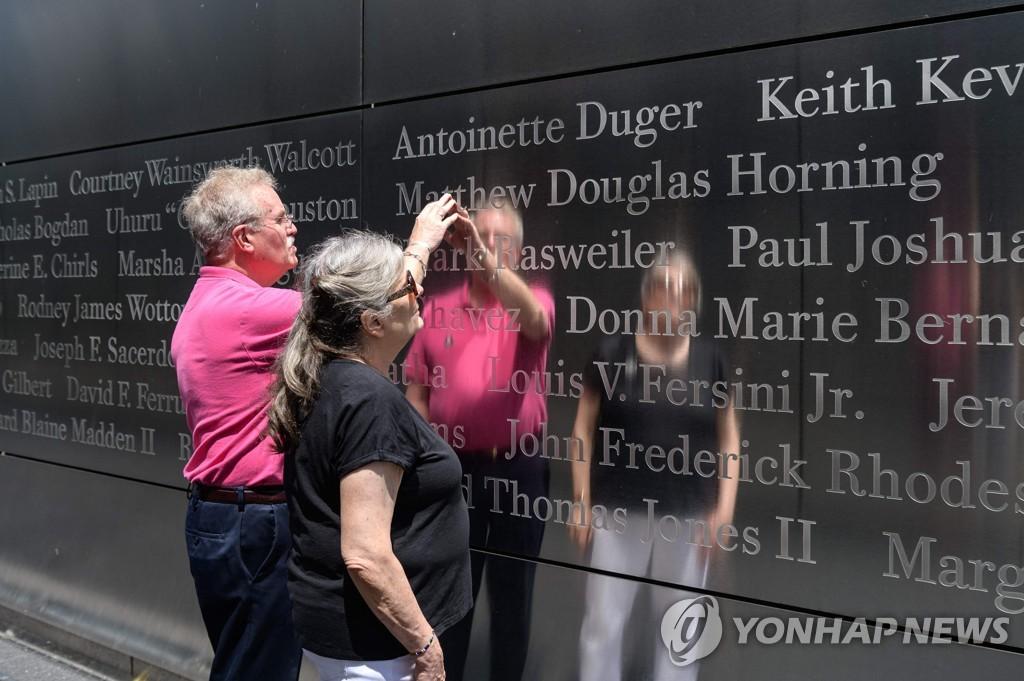 뉴저지주 9·11 추모 시설에서 아들의 이름을 가리키는 유가족