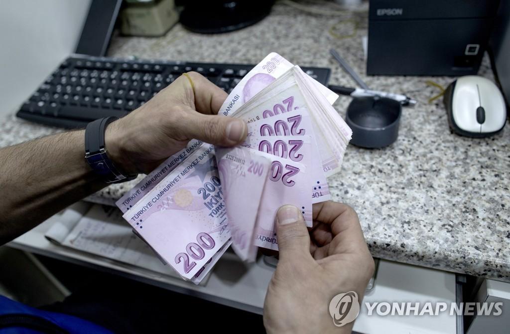 이스탄불의 한 환전상이 200리라 지폐를 세는 모습