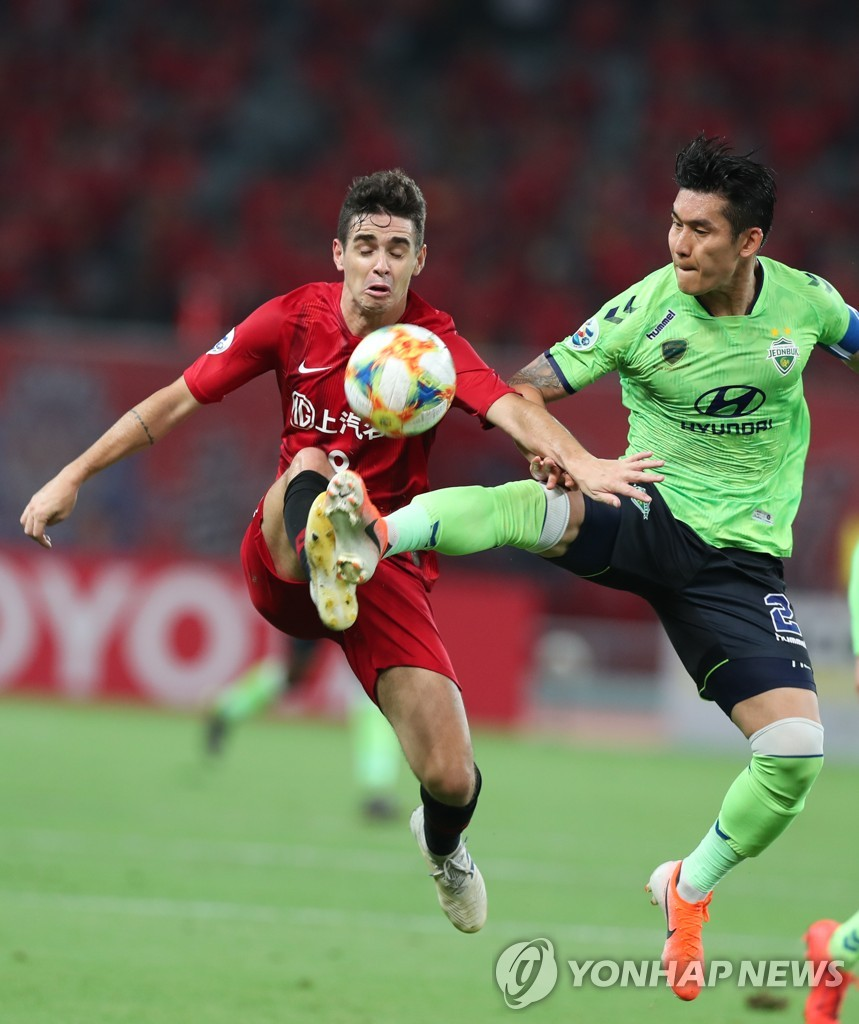 In this Xinhua photo, Lee Yong of Jeonbuk Hyundai Motors (R) battles Oscar of Shanghai SIPG for the ball during their round of 16 match in the Asian Football Confederation Champions League at Shanghai Stadium in Shanghai on June 19, 2019. (Yonhap)