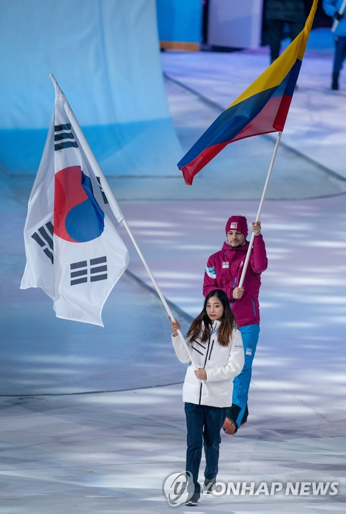 In this Olympic Information Service photo via Reuters, South Korean figure skater You Young (front) walks in with the national flag during the opening ceremony of the 2020 Winter Youth Olympics at Lausanne Vaudoise Arena in Lausanne, Switzerland, on Jan. 9, 2020. (PHOTO NOT FOR SALE) (Yonhap)