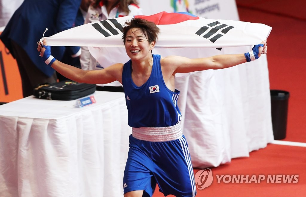 In this file photo from Sept. 1, 2018, South Korean boxer Oh Yeon-ji celebrates with the national flag after winning a gold medal in the women's 60-kilogram division at the 18th Asian Games at Jakarta International Expo Hall in Jakarta. (Yonhap)