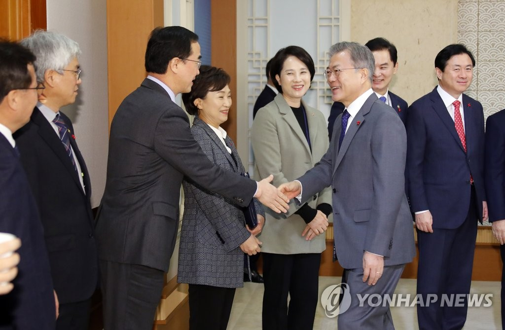 This photo, taken Jan. 8, 2019, shows President Moon Jae-in (R, front) shaking hands with Unification Minister Cho Myoung-gyon at a tea meeting ahead of a Cabinet meeting. (Yonhap)