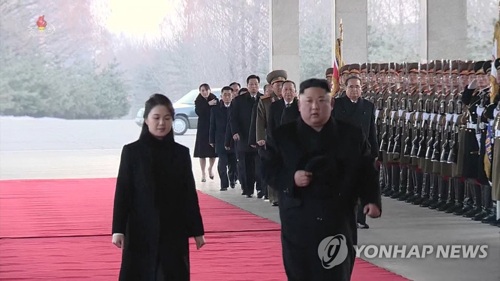 This image, captured from footage of North Korea's central TV station on Jan. 8, 2019, shows the North's leader Kim Jong-un (R) and his wife Ri Sol-ju, leaving Pyongyang at a train station for a four-day trip to China. (For Use Only in the Republic of Korea. No Redistribution) (Yonhap)