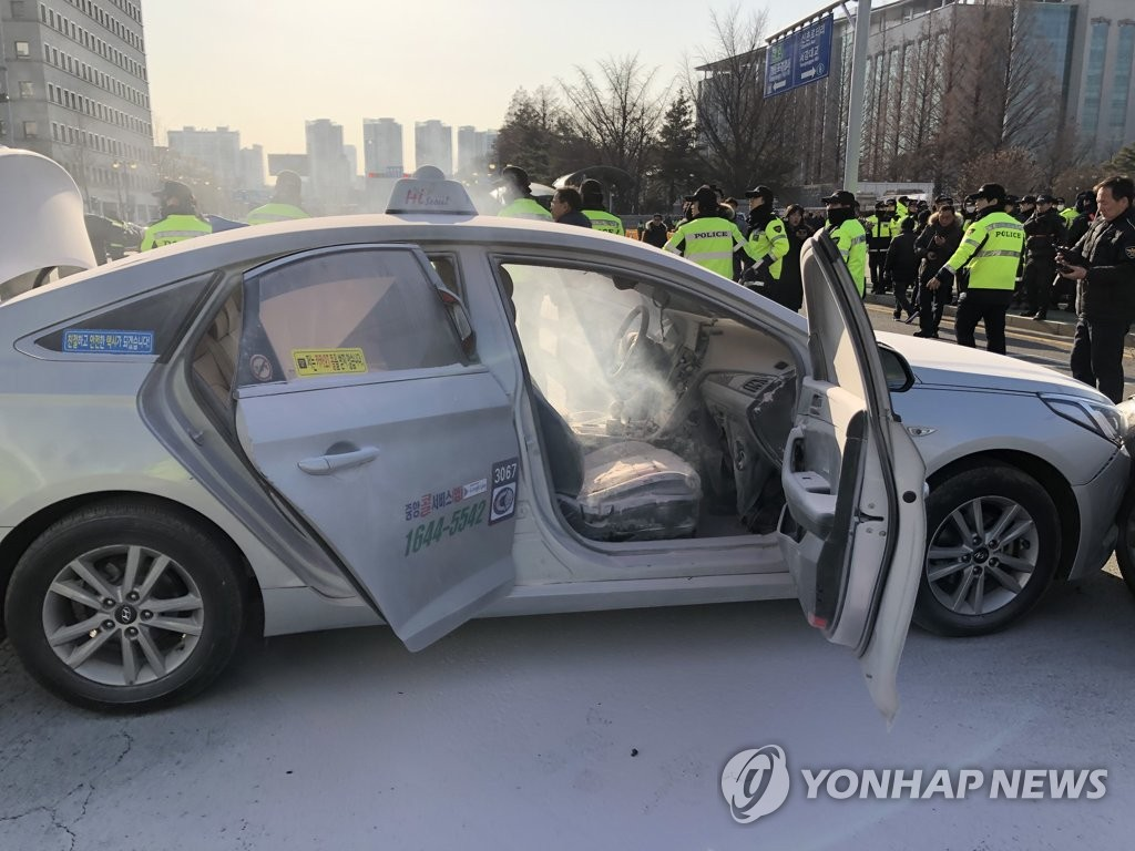 The photo, taken Feb. 11, 2019, shows a taxi after a fire set by the driver was put out by firefighters near the National Assembly in western Seoul. (Yonhap)