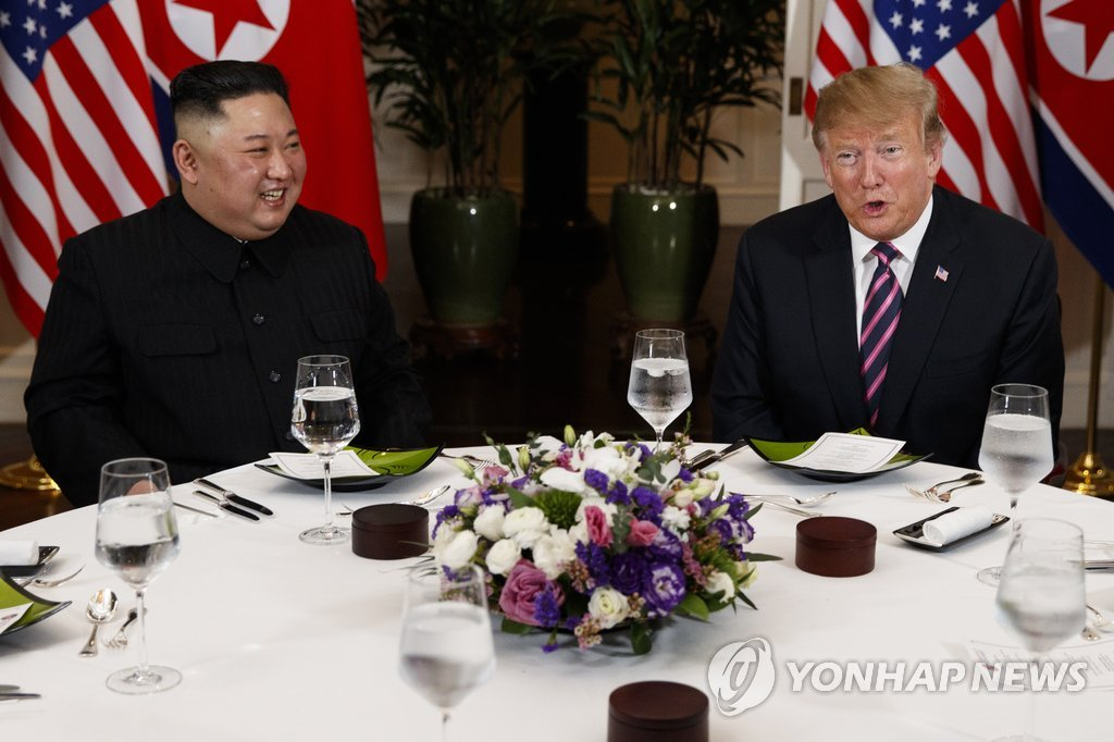 This photo, released by the Associated Press, shows U.S. President Donald Trump (R) speaking with North Korean leader Kim Jong-un during a dinner in Hanoi, Vietnam, on Feb. 27, 2019. (Yonhap)