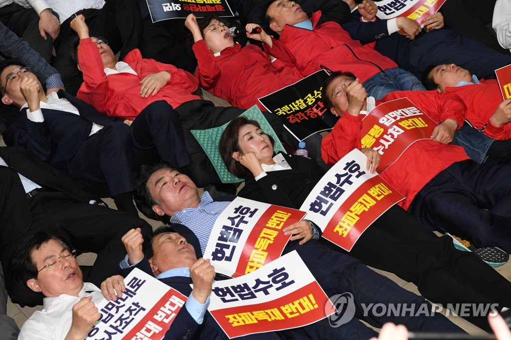 Lawmakers of the main opposition Liberty Korea Party lie down at the National Assembly on April 30, 2019, to block other parties' lawmakers from entering a meeting room for the designation of an election reform bill as a fast-track measure. (Yonhap)