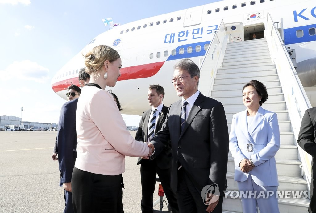 South Korean President Moon Jae-in (R) shakes hands with Katri Kulmuni, the Finnish minister of economic affairs and employment, shortly after arriving at the Helsinki airport on June 9, 2019. (Yonhap)