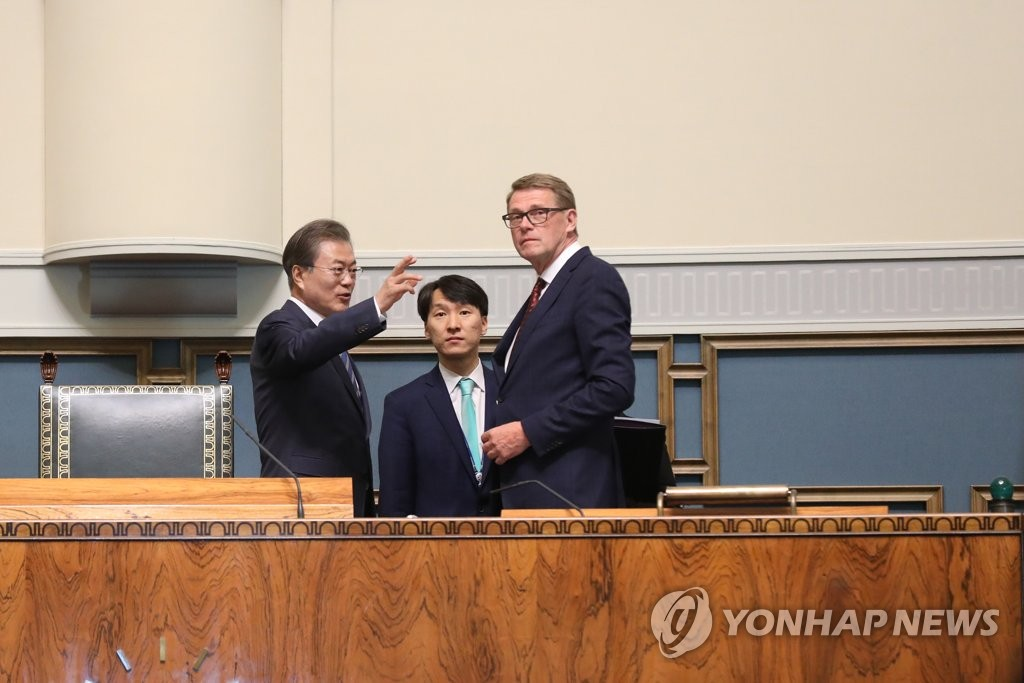 South Korean President Moon Jae-in talks with Matti Vanhanen, speaker of the Finnish parliament, during a visit to the Parliament House in Helsinki on June 10, 2019. (Yonhap)