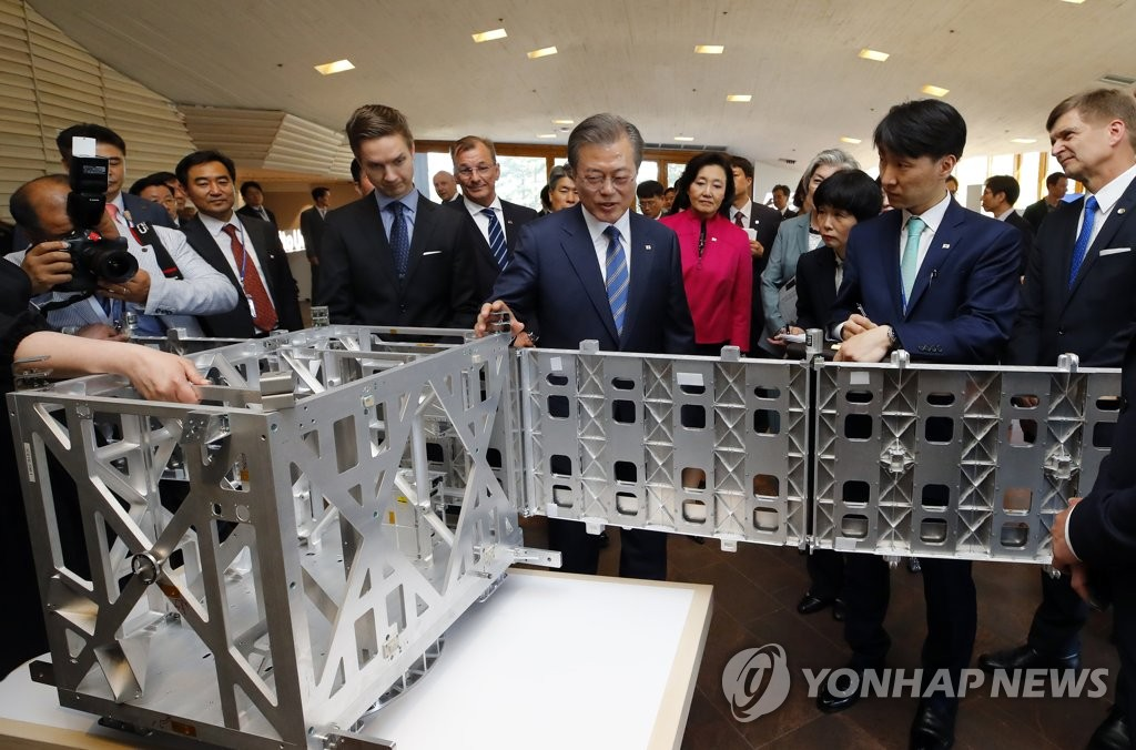 South Korean President Moon Jae-in looks around the booth of ICEYE, a satellite startup, at the Otaniemi research zone, a suburb of Helsinki, on June 10, 2019. (Yonhap)