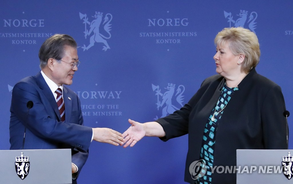 South Korean President Moon Jae-in (L) shakes hands with Norwegian Prime Minister Erna Solberg after a post-summit joint press conference in Oslo on June 13, 2019. (Yonhap)