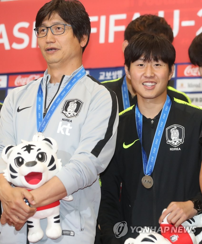 In this file photo from June 17, 2019, Chung Jung-yong (L) then head coach of the South Korean men's under-20 national football team, and midfielder Lee Kang-in pose for photos at Incheon International Airport after returning from the FIFA U-20 World Cup in Poland. South Korea finished second to Ukraine in the tournament. (Yonhap)
