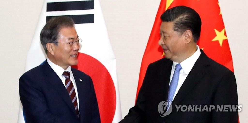 会談を前に握手を交わす文在寅大統領(左)と習近平国家主席=27日、大阪(聯合ニュース)
