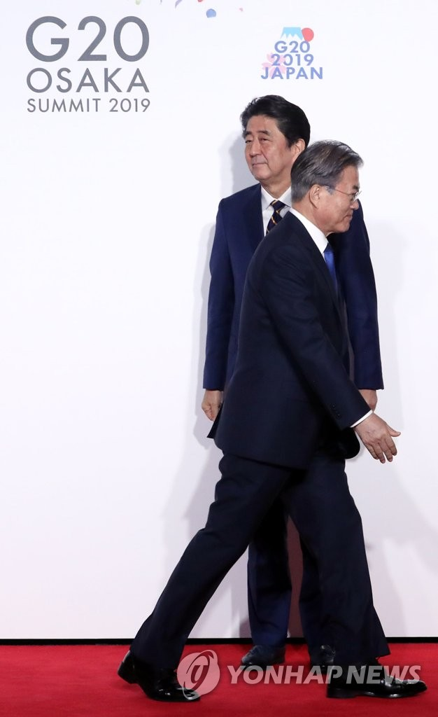 This file photo, dated June 28, 2019, shows South Korean President Moon Jae-in (front) walking away from Japanese Prime Minister Shinzo Abe after being greeted at the venue for a Group of 20 summit in Osaka, Japan. (Yonhap)