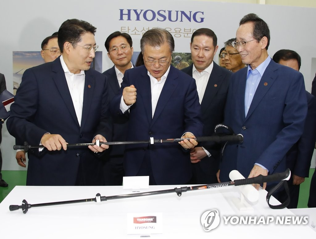 President Moon Jae-in (C) is briefed on a material using carbon fiber during an event on Hyosung Group's plan to sharply increase investment in its related business. It was held in Jeonju, North Jeolla Province, on Aug. 20, 2019. (Yonhap)