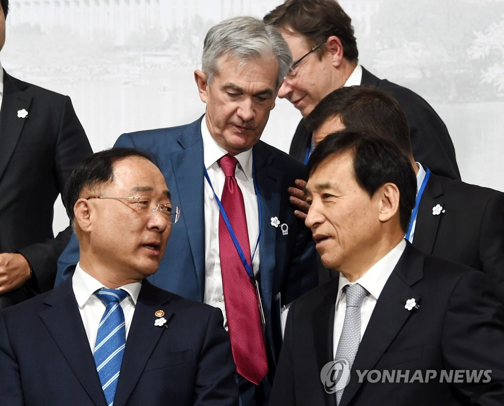 In the photo provided by the Finance Ministry, Bank of Korea Gov. Lee Ju-yeol (R) and South Korean Finance Minister Hong Nam-ki (L) are seen posing for a group photo at the Group of 20 Finance Ministers and Central Bank Governors' Meeting in Washington on Oct. 17, 2019. (PHOTO NOT FOR SALE) (Yonhap)