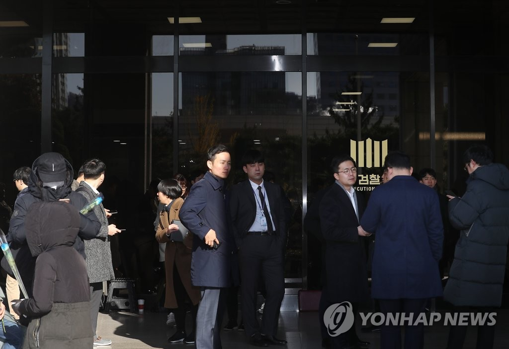 Journalists are seen waiting in front of the Seoul Central District Prosecutors Office in central Seoul on Nov. 14, 2019. Supporters of former justice minister Cho Kuk are also seen holding flowers. (Yonhap)