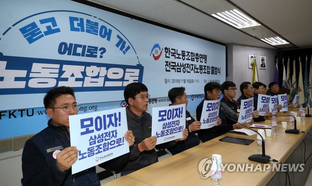 Participants at a ceremony marking the launch of a labor union of Samsung Electronics Co. under one of South Korea's two largest umbrella labor unions hold up signs with slogans in Seoul on Nov. 16, 2019. (Yonhap)