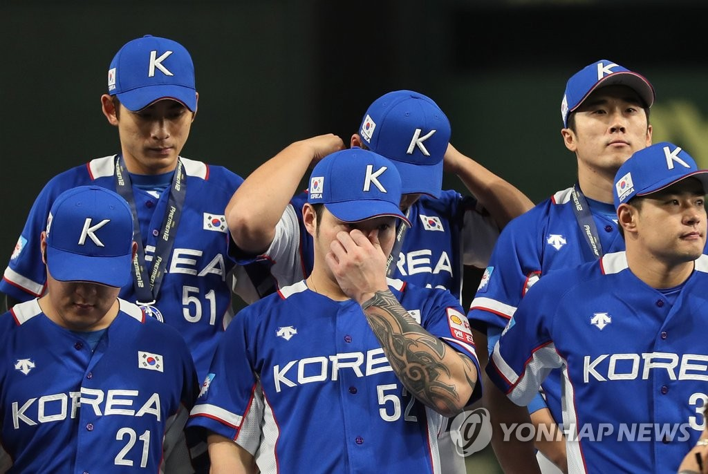 Park Byung-ho of South Korea (C, first row) wipes away tears during the medal ceremony of the World Baseball Softball Confederation (WBSC) Premier12 at Tokyo Dome in Tokyo on Nov. 17, 2019, following South Korea's 5-3 loss to Japan in the final. (Yonhap)