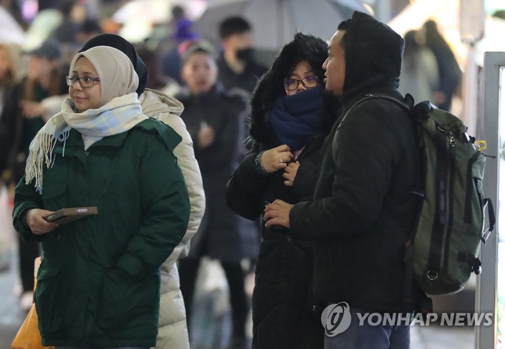 Foreign visitors wear thick winter clothes as they walk on a Seoul street on Dec. 1, 2019. (Yonhap)